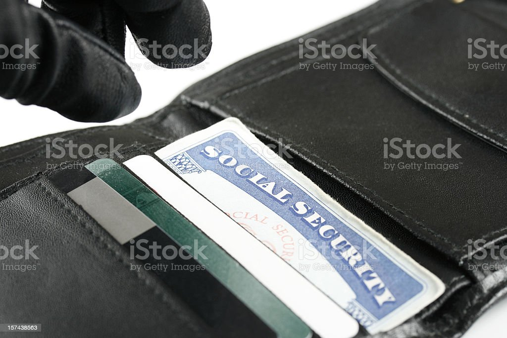 Identity Thief's Hand Reaching for Social Security Card in Wallet stock photo