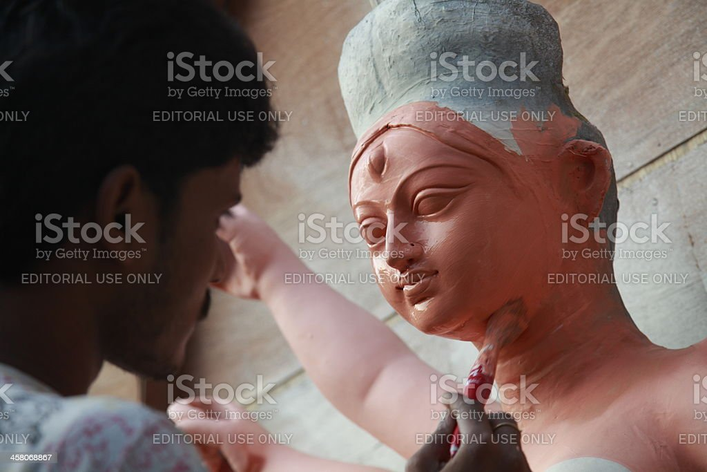 Idol maker painting a clay model of Hindu goddess Durga royalty-free stock photo