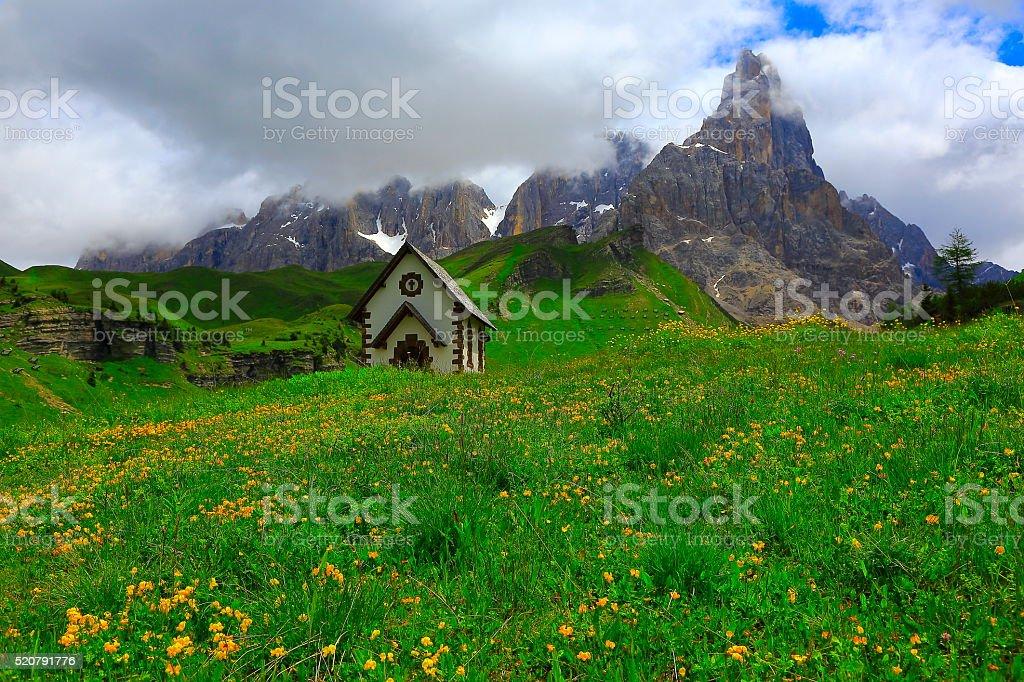 Idyllic Alpine church and flowers spring, Dolomites, Italian Tirol alps stock photo