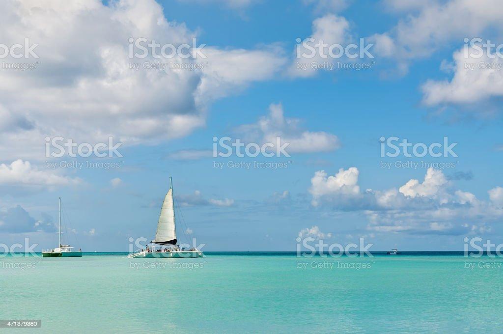 Idyllic blue beach with boats, Aruba island - Caribbean sea stock photo