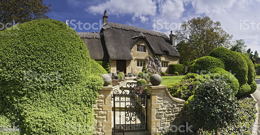 Idyllic country cottage thatched roof pretty summer gardens Cotswolds UK stock photo