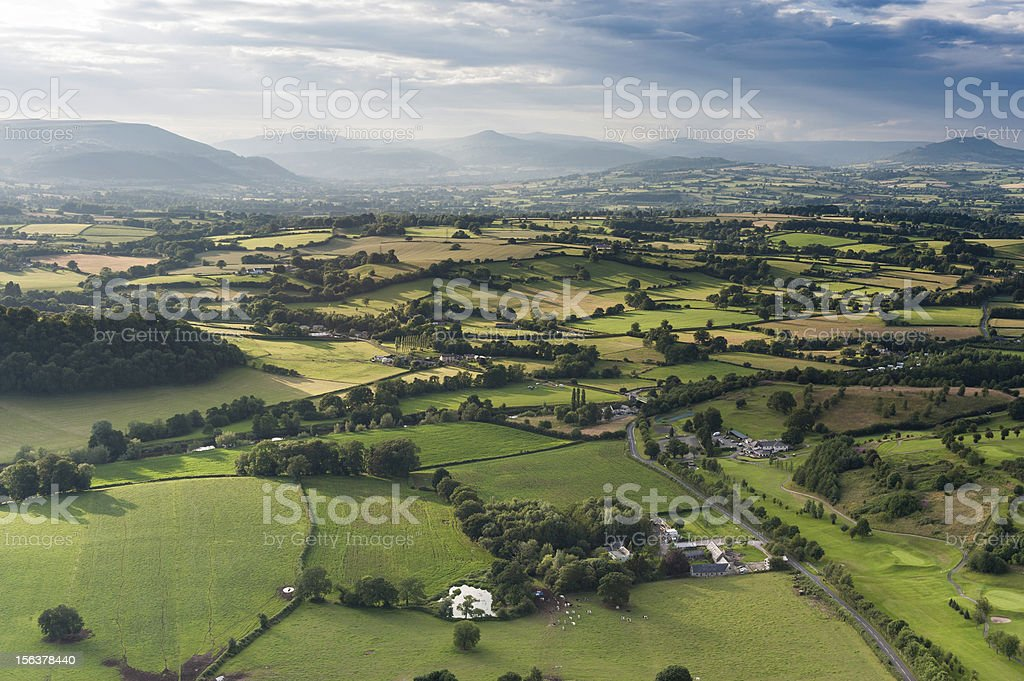 Idyllic country meadows misty mountains aerial landscape stock photo