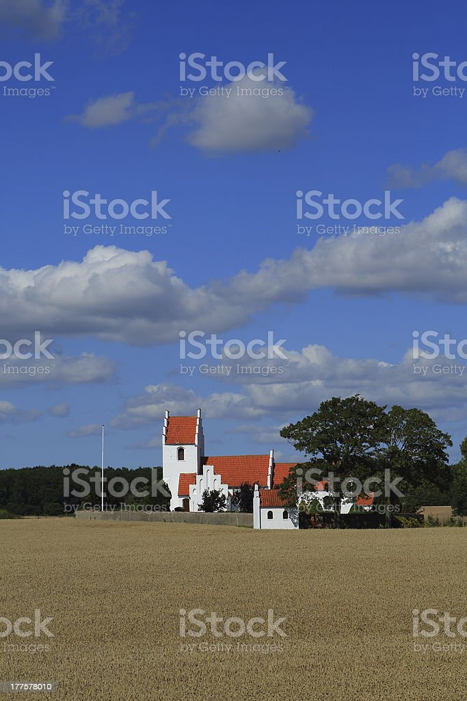 Idyllic country side parish church behind wheat field royalty-free stock photo