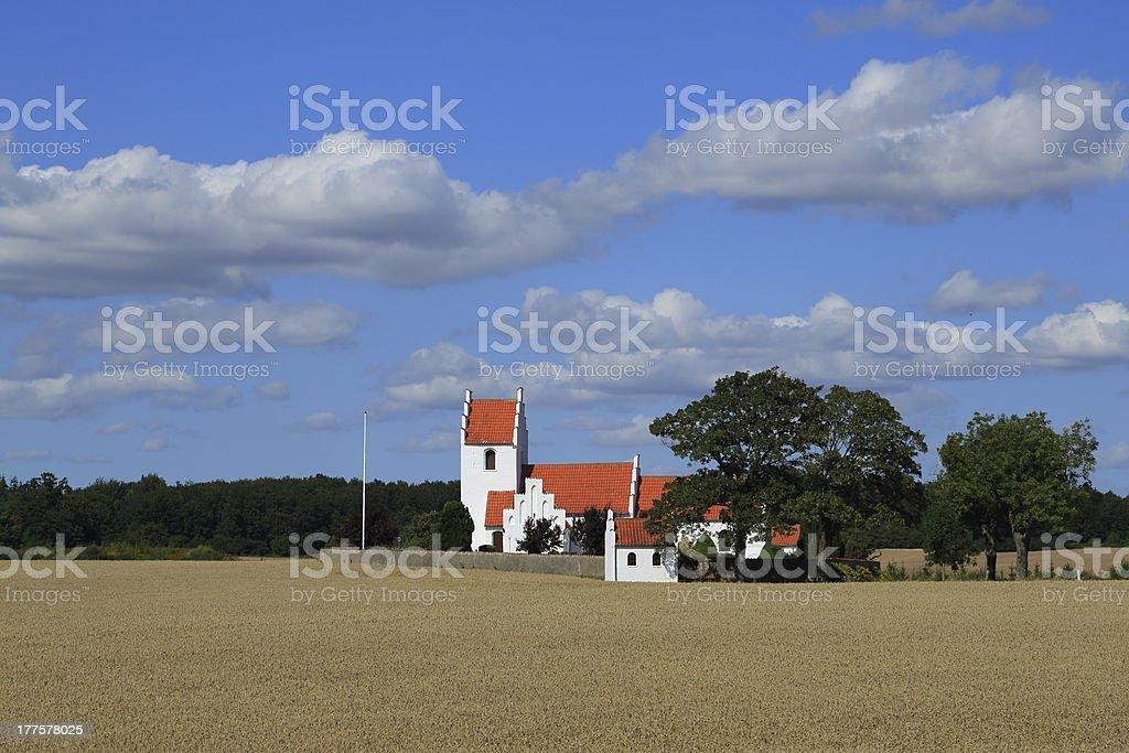 Idyllic country side parish church behind wheat field royalty-free stock photo