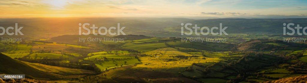 Idyllic green hills pasture mountain ridges illuminated by sunset panorama stock photo