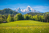 Idyllic landscape in the Alps with mountain chalet in springtime