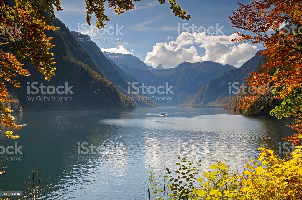 Idyllic mountain lake autumn colours framed by leaves stock photo
