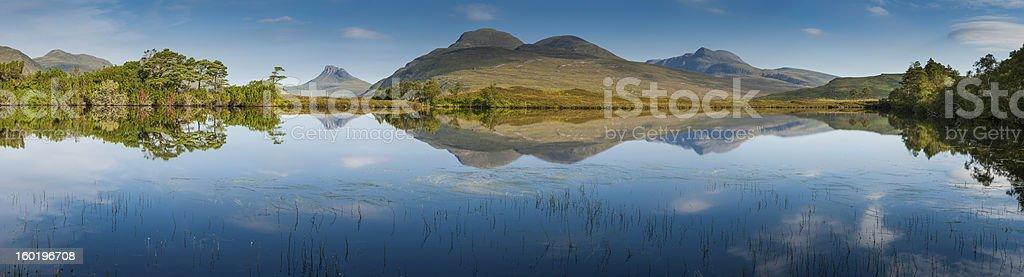 Idyllic mountain lake reflected Highland peaks panorama Scotland stock photo