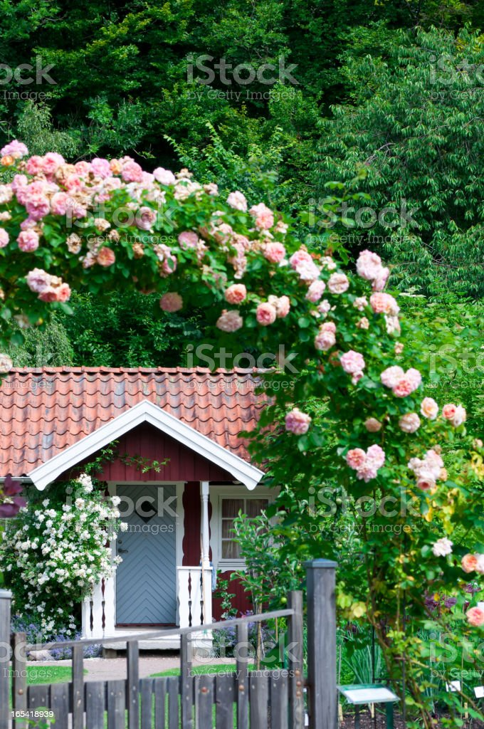 Idyllic red cottage in botanical garden stock photo