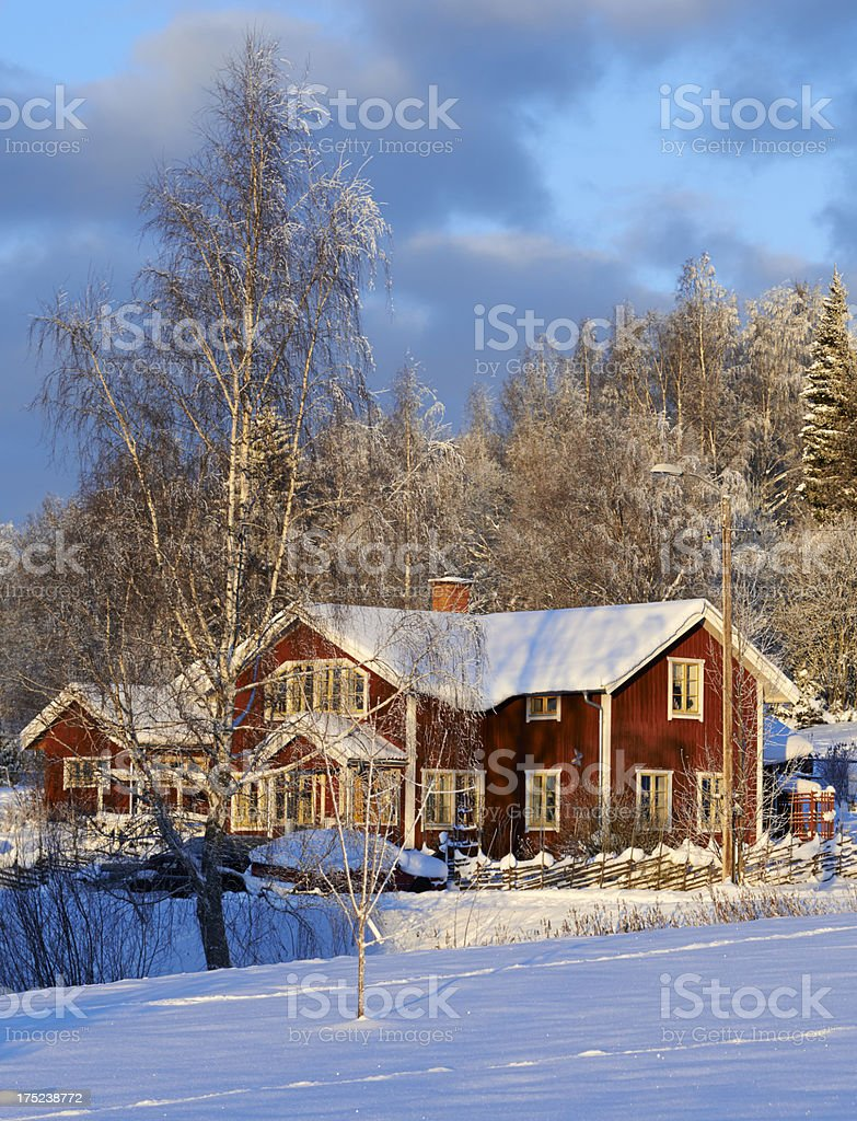 Idyllic Red Swedish House against a winter forest - vertical stock photo