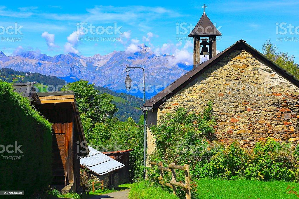 Idyllic rustic Alpine village stone church, Mont Blanc Massif stock photo