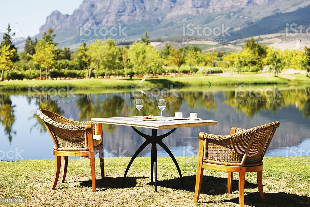 Idyllic scene with table and chairs by serene lake stock photo