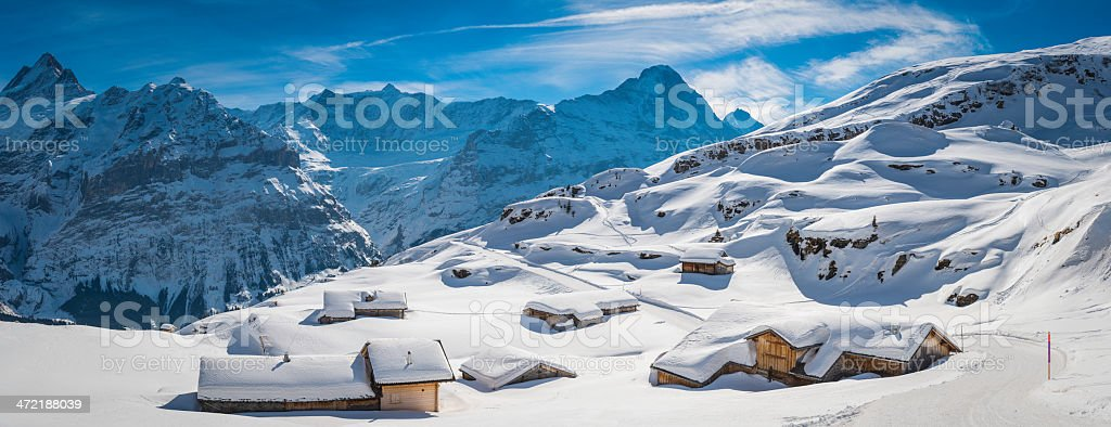 Idyllic snowy mountain chalets in Alpine village Alps Switzerland stock photo