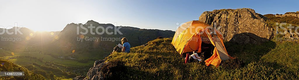 Idyllic summer camping child reading in mountains royalty-free stock photo