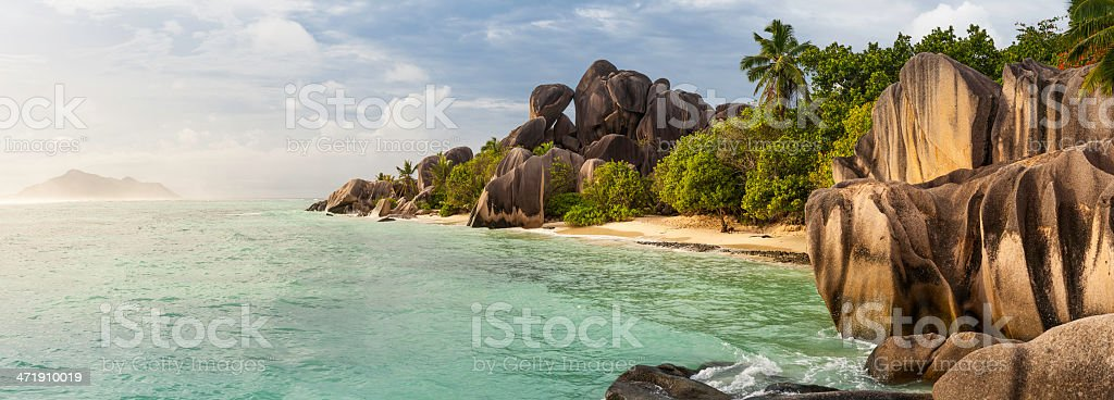 Idyllic tropical island beach remote ocean cove palm trees panorama royalty-free stock photo