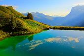 Idyllic turquoise lake reflection above Grindelwald valley: Swiss Alps sunrise