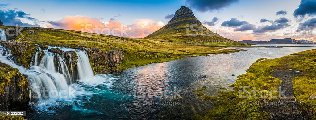 Idyllic waterfall sunrise cloudscape beside mountain peak panorama Kirkjufell Iceland stock photo