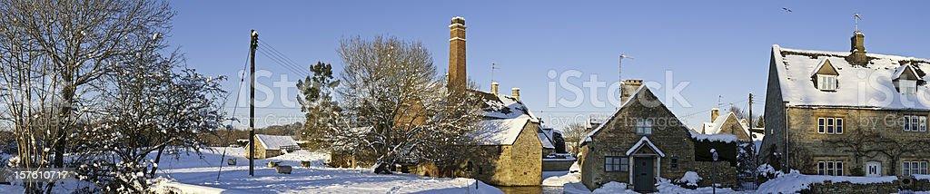 idyllic winter village cottages watermill crisp white snow Cotswolds UK stock photo