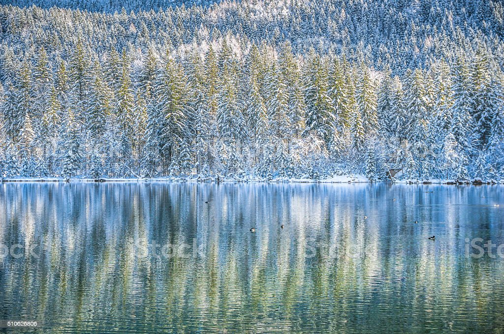 Idyllic winter wonderland with mountain lake and snow covered trees stock photo