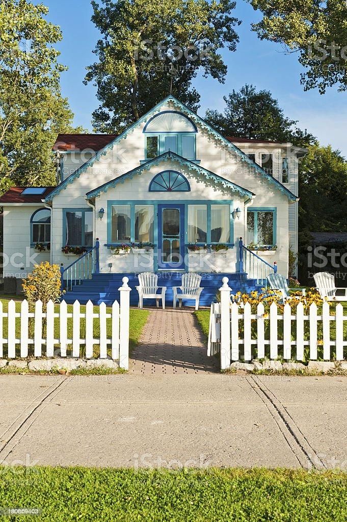 Idyllic wooden cottage white picket fence stock photo