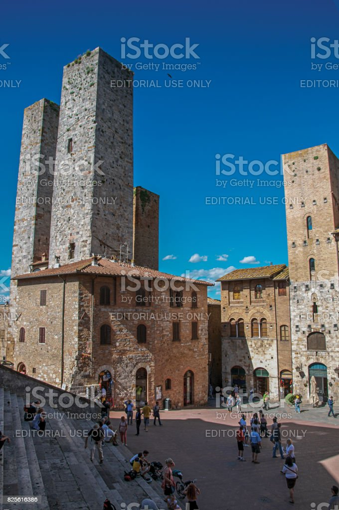 iew of square with people, old buildings and towers in San Gimignano stock photo