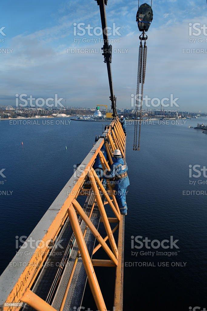 Iinstallers steeplejacks work on installing jib construction tower crane. stock photo