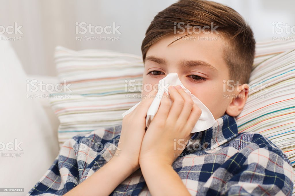 ill boy blowing his nose at home stock photo