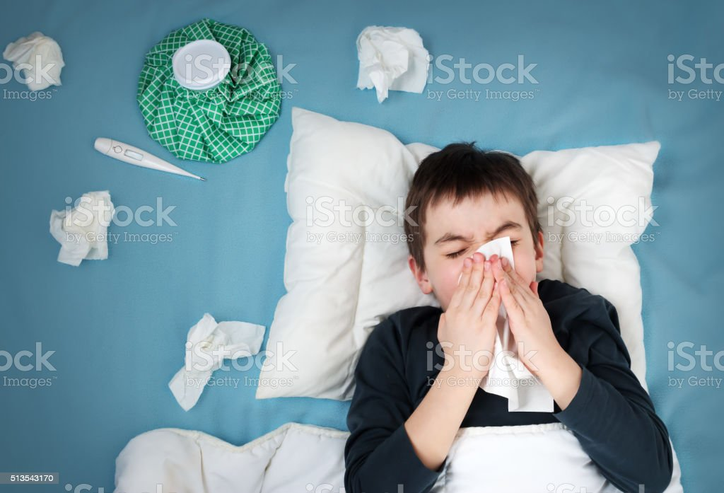 Ill boy lying in bed stock photo