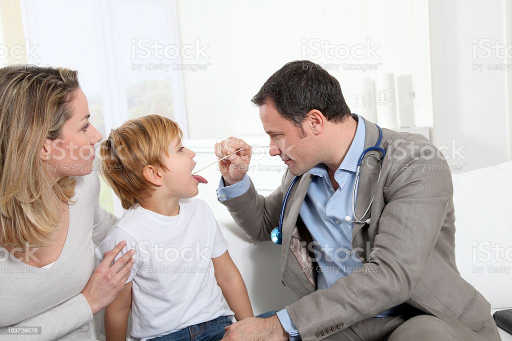 Ill little boy at home with doctor stock photo