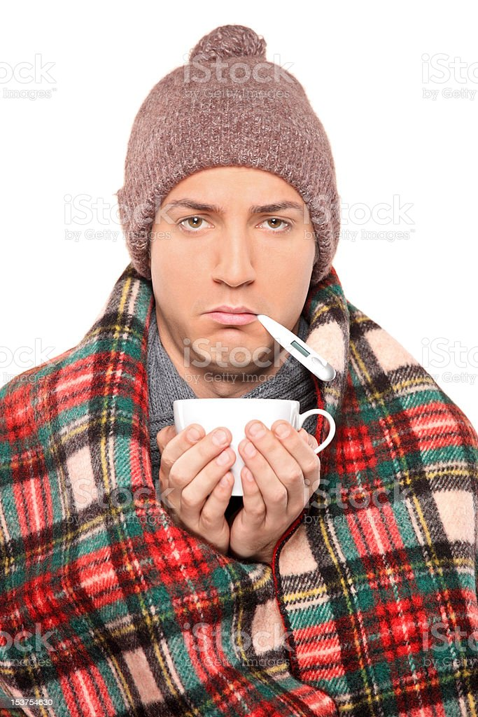 Ill man covered with blanket holding a tea cup royalty-free stock photo
