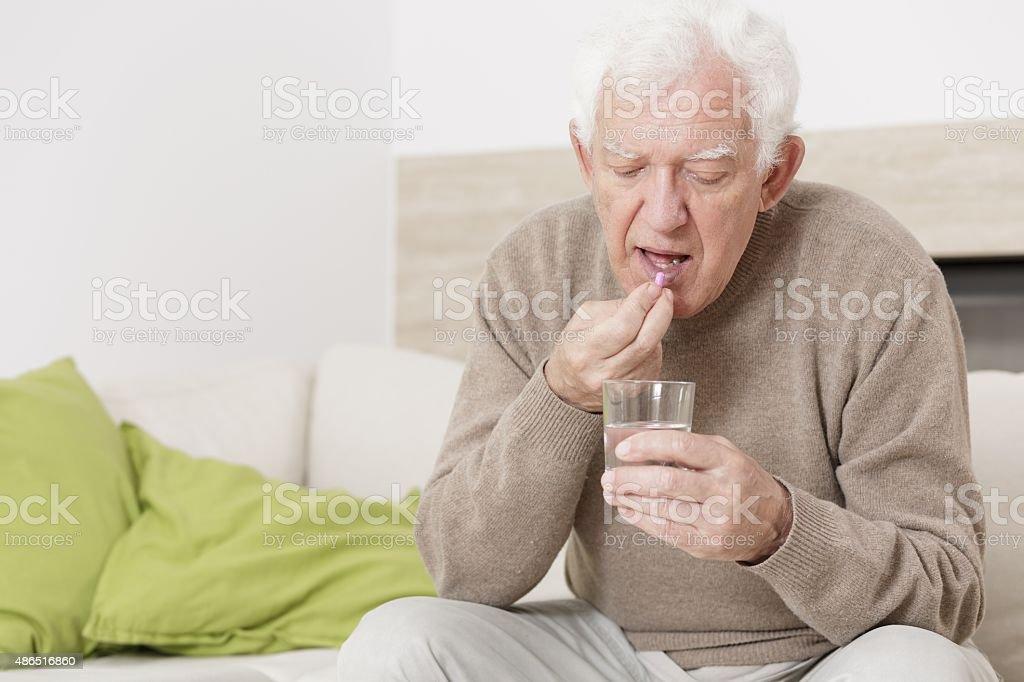 Ill man taking medicine stock photo