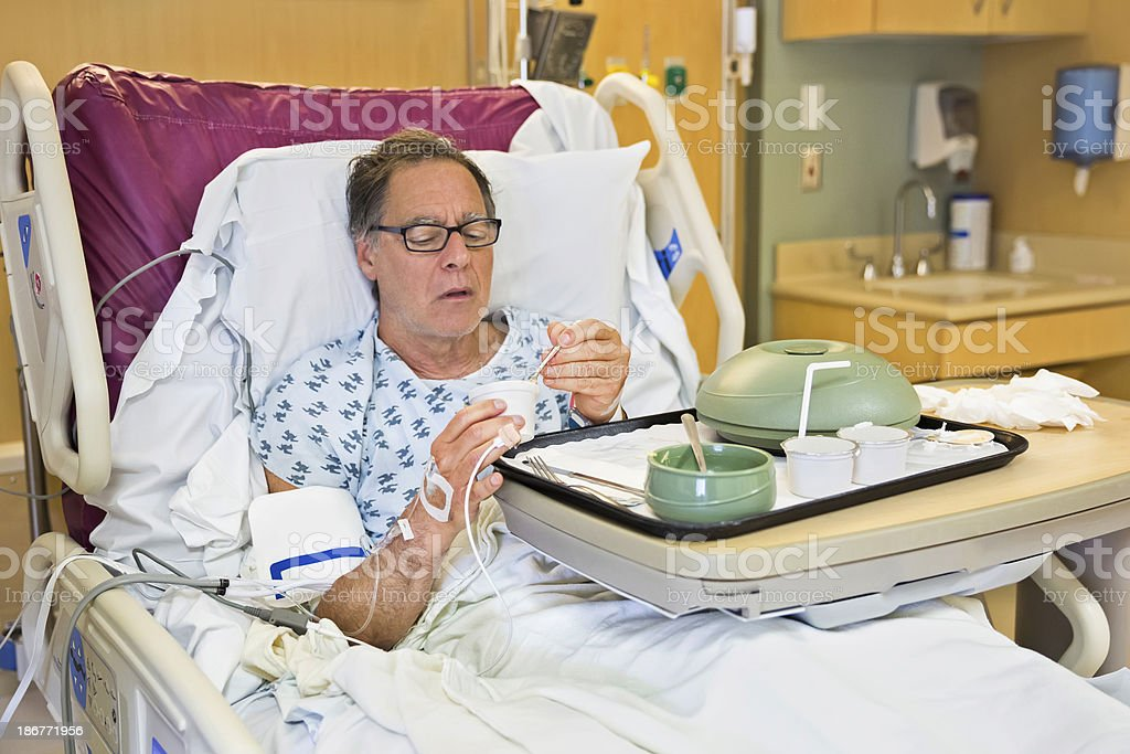 Ill senior man eating a meal in the hospital stock photo