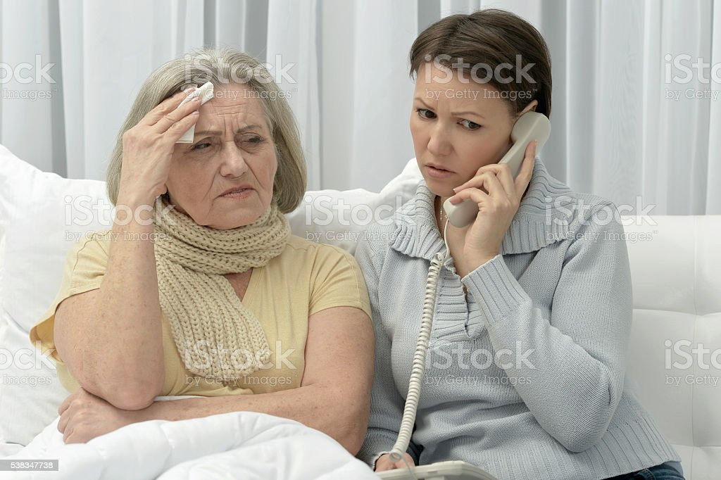 ill Senior woman and worried daughter stock photo