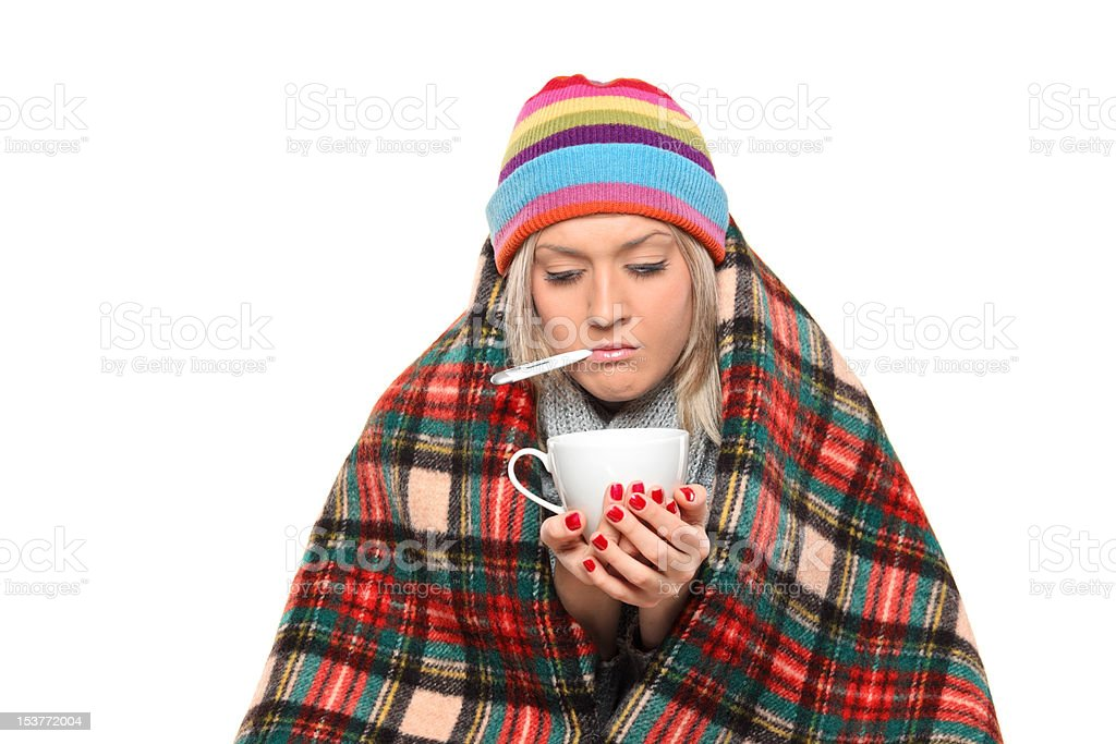 Ill woman covered with blanket holding a tea cup stock photo