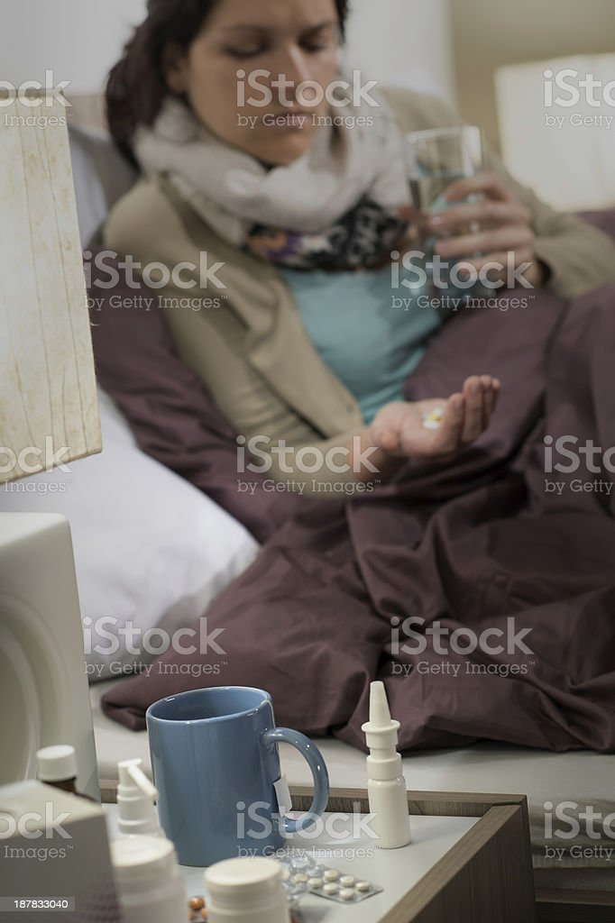 Ill woman in bedroom with flu pills royalty-free stock photo