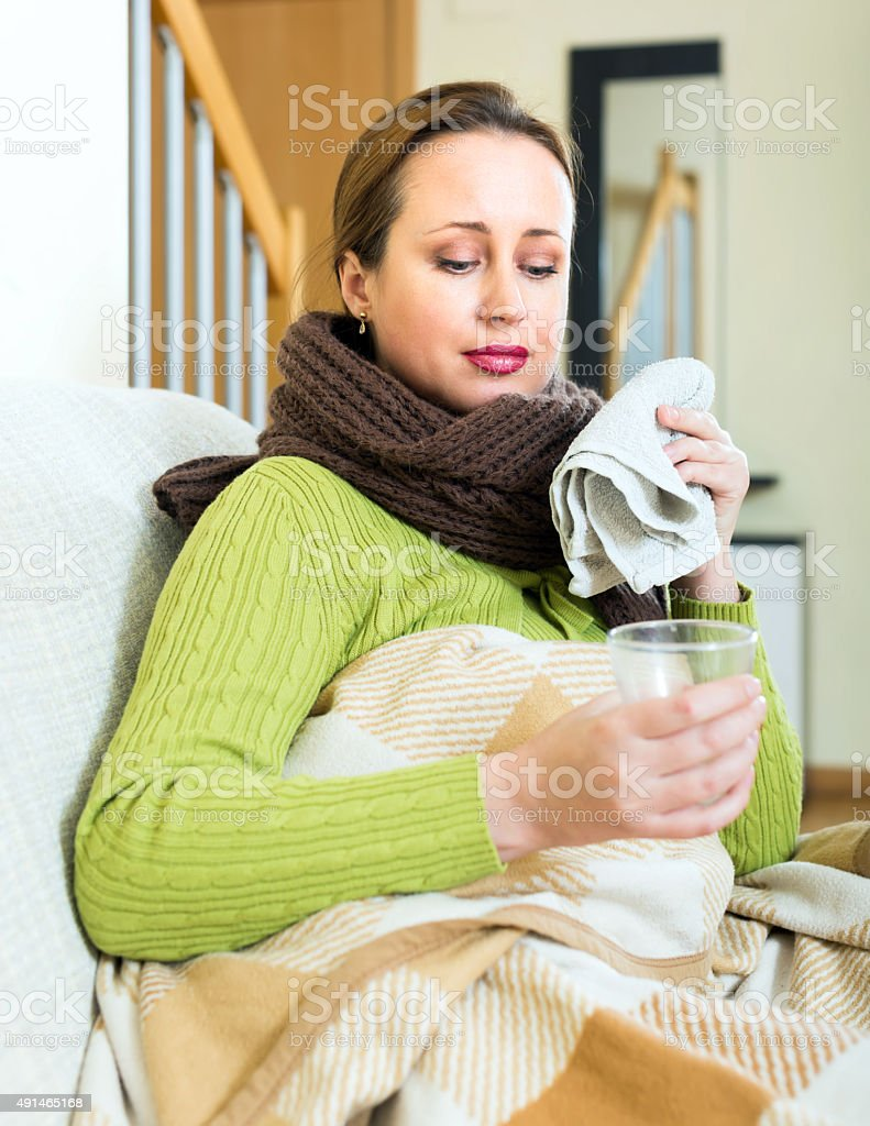 Ill woman with a warm drink stock photo