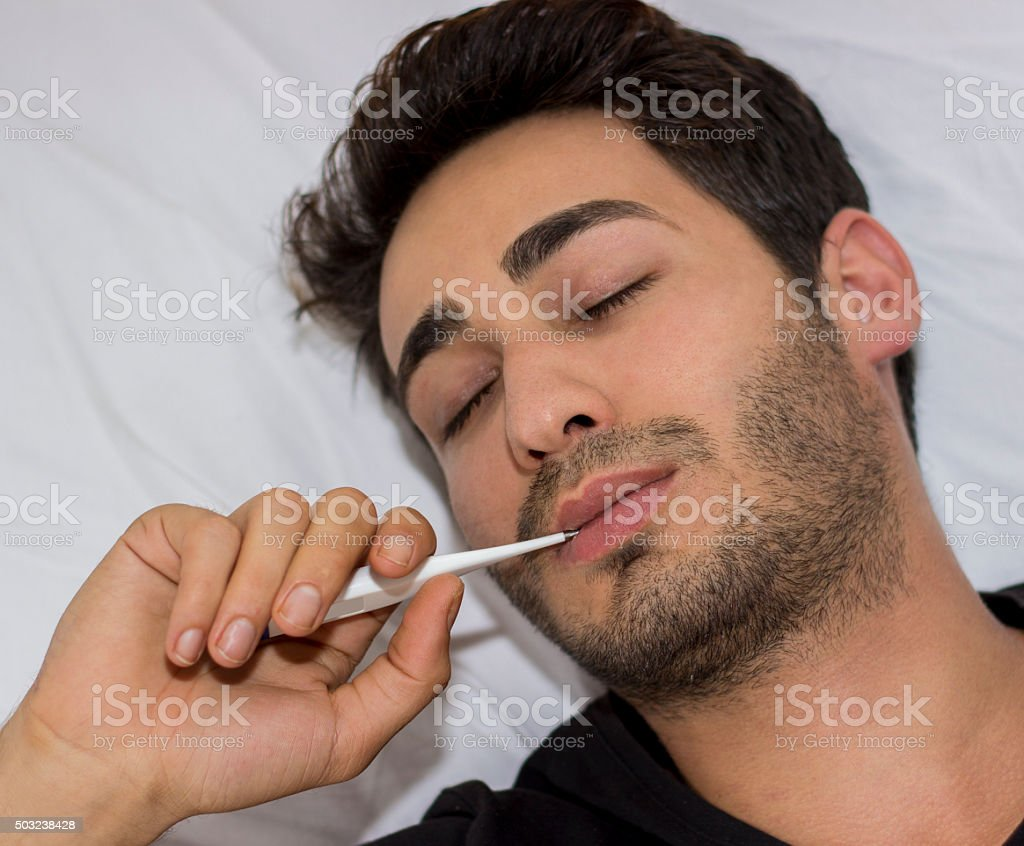 Ill young man testing with thermometer. stock photo