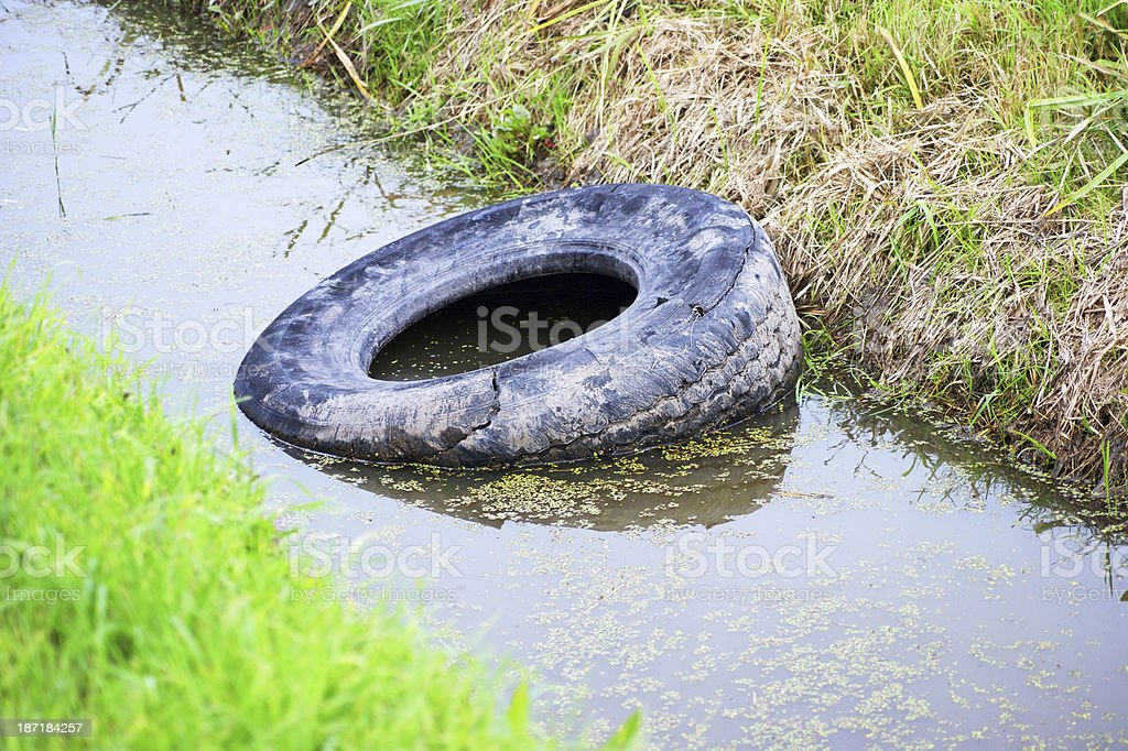 Illegal Roadside Dumping of  tractor tire royalty-free stock photo