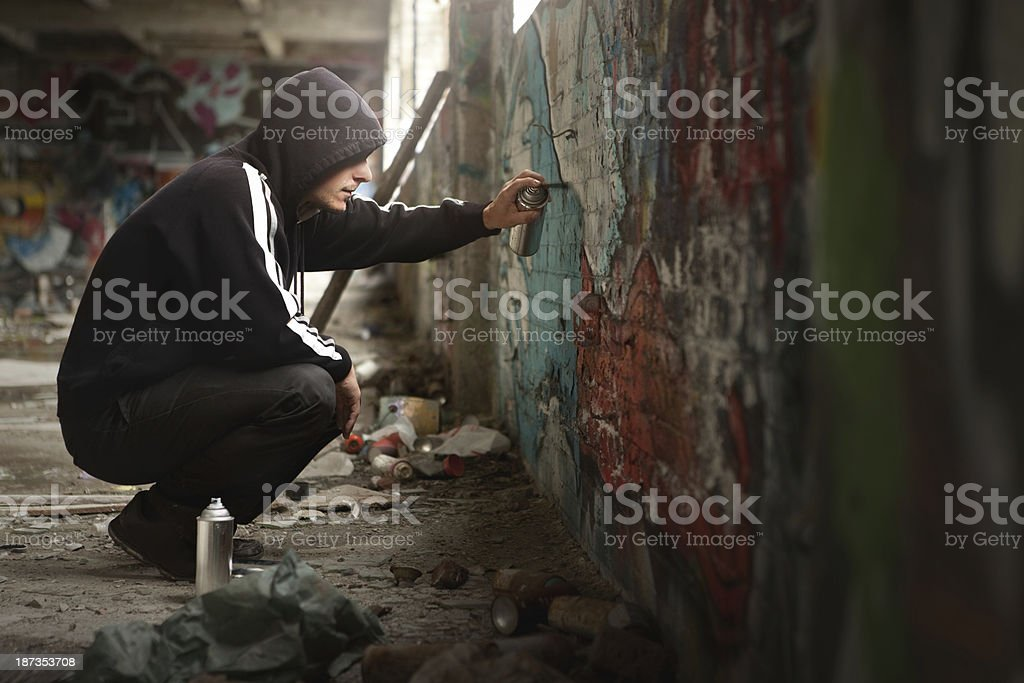 Illegal Young man Spraying paint on a Graffiti wall. stock photo