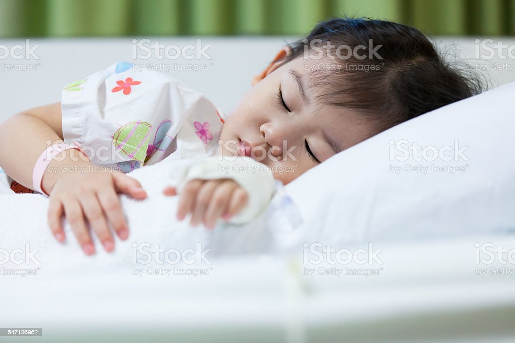 Illness child in hospital, saline intravenous (IV) on hand asian stock photo