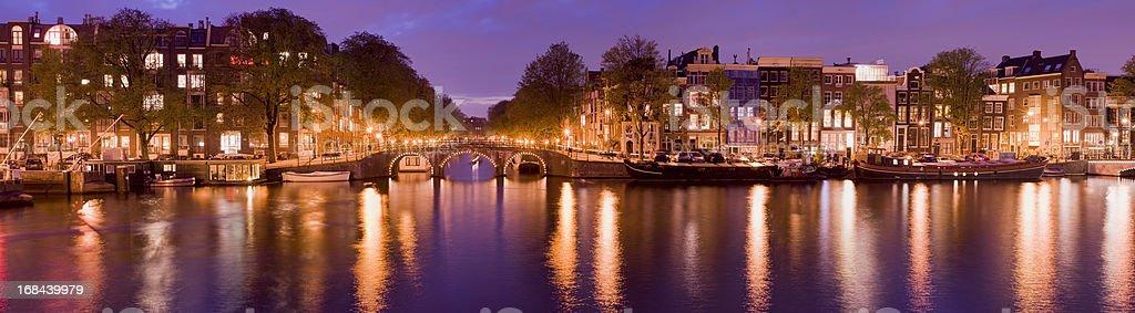 Illuminated Amsterdam Canal at dusk. stock photo