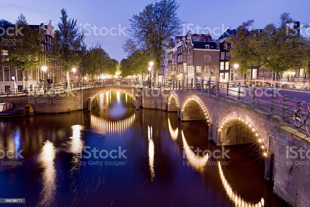 Illuminated Amsterdam Canal Bridges at Night Holland stock photo