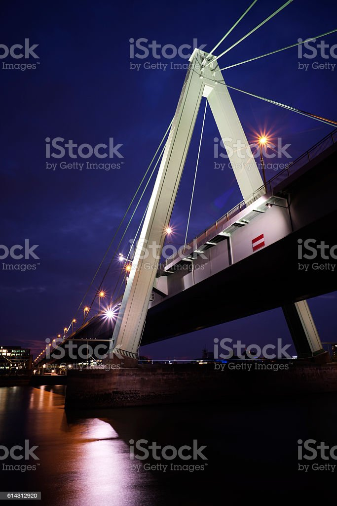 Illuminated bridge across Rhine river in Cologne at dusk stock photo