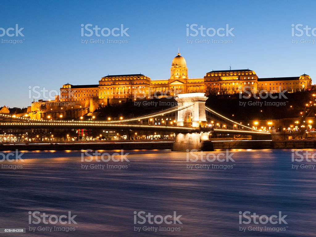 Illuminated Buda Castle and Chain Bridge over Danube River in stock photo