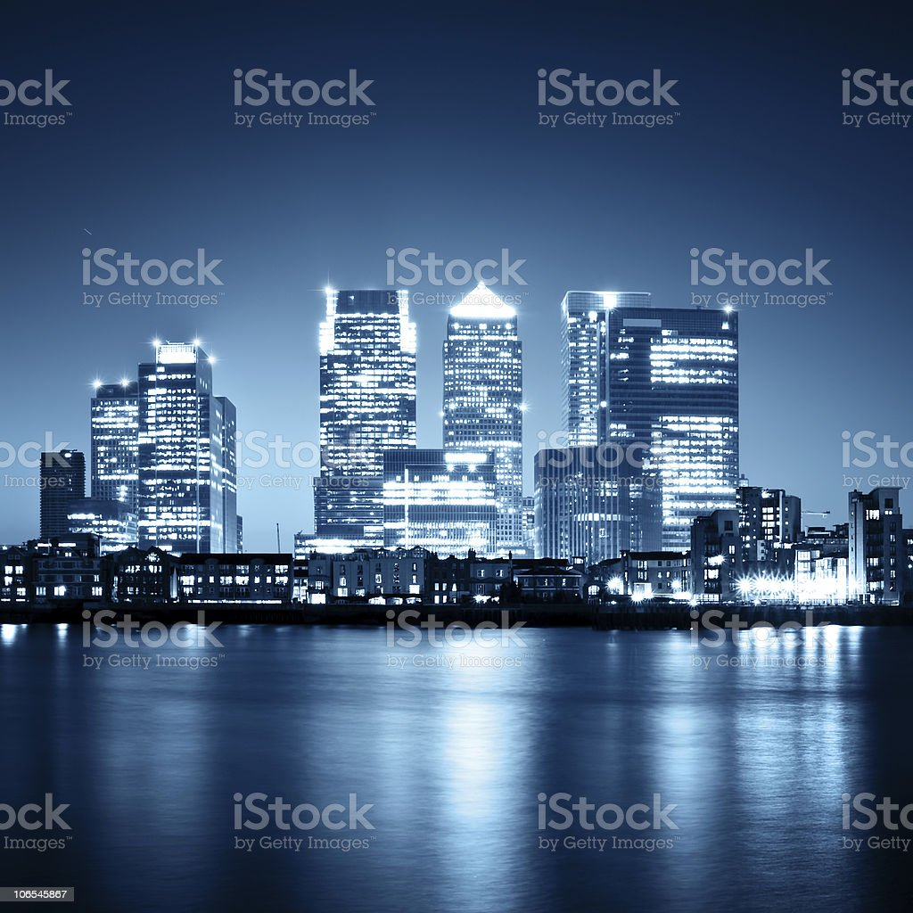 Illuminated Canary Wharf skyline in London at night stock photo