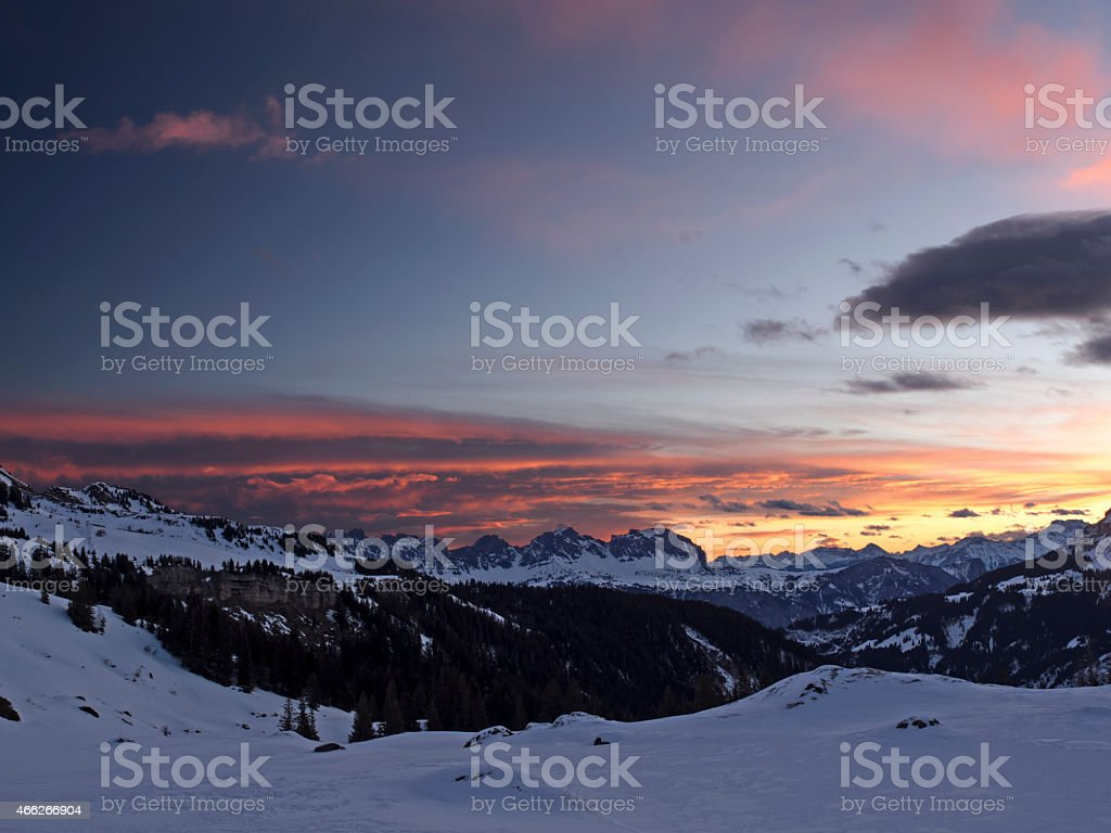 Illuminated clouds at sunrise over snowy mountains stock photo