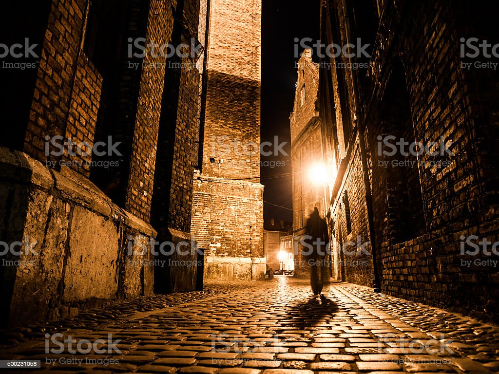 Illuminated cobbled street in old city by night stock photo
