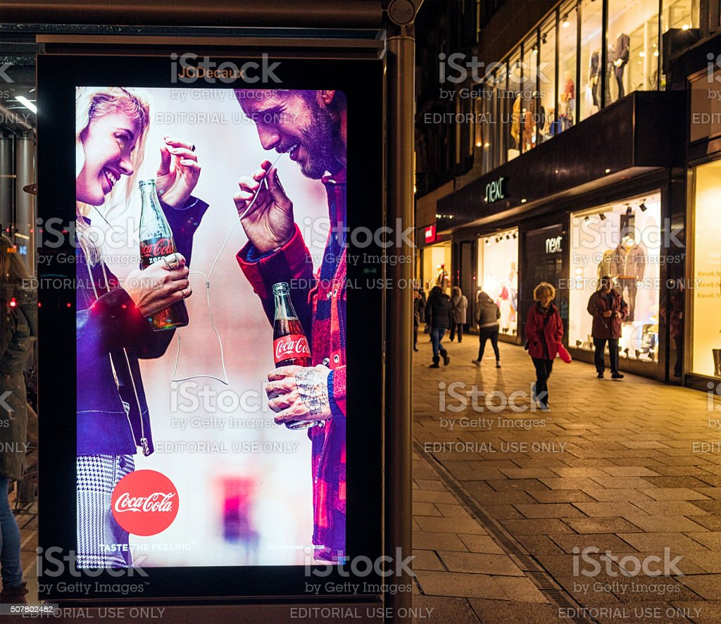 Illuminated Coca-Cola advertisement at night stock photo