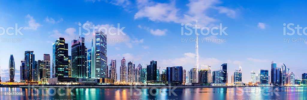 Illuminated Dubai city skyline at sunset, United Arab Emirates. stock photo