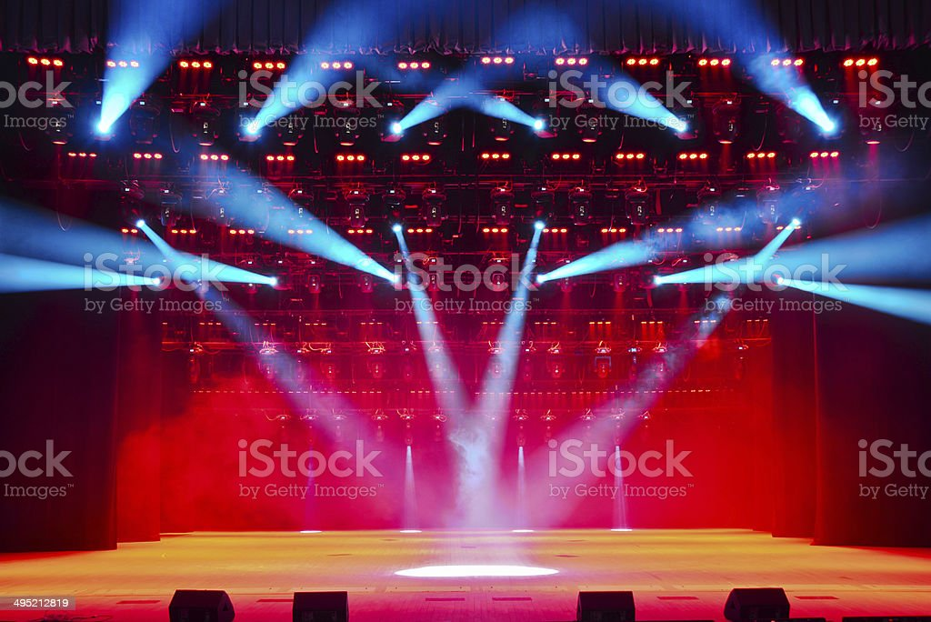 Illuminated empty theater stage with smoke stock photo